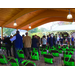 People gather under the pavilion, chairs with green bags attached are lined up neatly