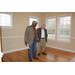 Two men standing inside the property in an empty room with hardwood floors