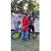 A young boy poses with his new bike with 2 little boys standing behind him