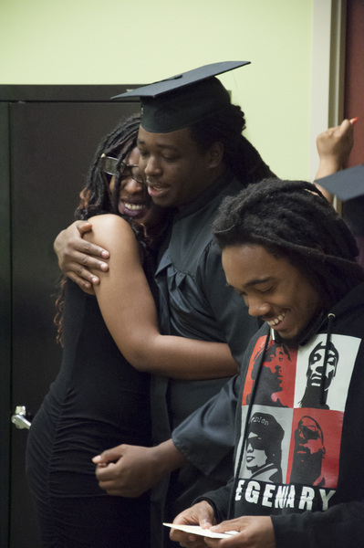A man wearing a cap and gown embracing a young woman with a man smiling next to them