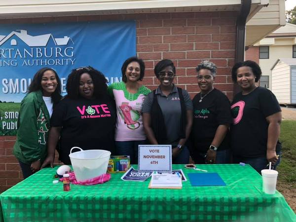 6 ladies standing in front of a table with Vote November 6th signs
