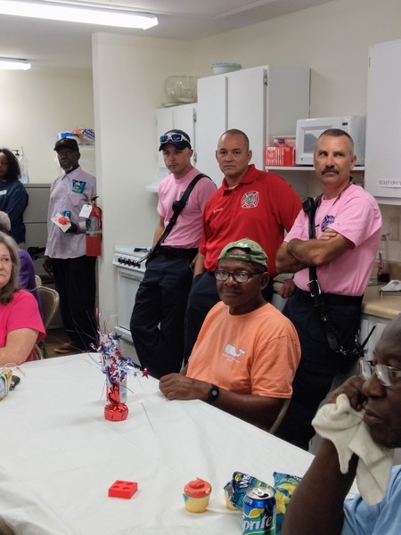 Attendees gathered around a table while Emergency Workers stand behind them, two wearing pink shirts and one wearing a red shirt