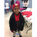 A little boy wearing a red stocking hat with a black jacket with a black and red vest under it and red gloves
