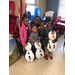 Four children with their mother pose with 3 stuffed snowmen