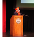 A lady with a red hat speaking at the podium